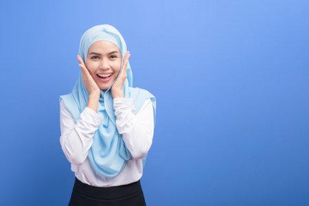 Photo pour Portrait of a young muslim woman with hijab over blue background studio. - image libre de droit