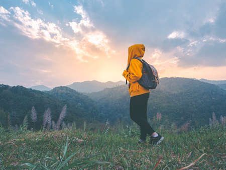 Photo for woman hiking with backpack relaxing in nature and enjoy the sunset view on mountain peak at Mae Wong national park Thailand. - Royalty Free Image