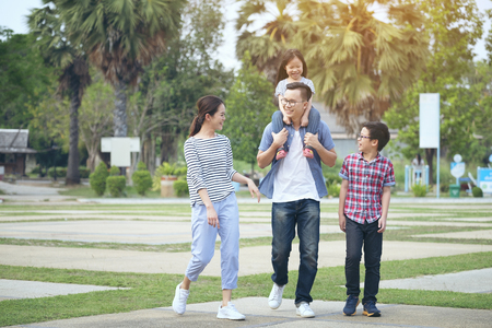 Photo for family running through garden at park, Happy family in the park, Mother, father and smiling - Royalty Free Image