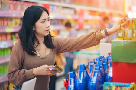 Photo pour woman making shopping decision for sweet in supermarket, stands in store - image libre de droit