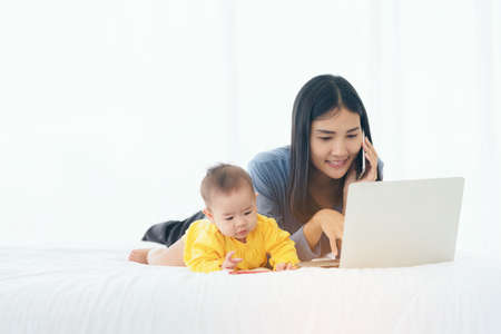 Photo pour Mom and baby with laptop computer working from home - image libre de droit