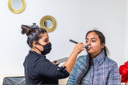 Foto de woman dressed in black blouse putting makeup on another younger woman in a white room - Imagen libre de derechos
