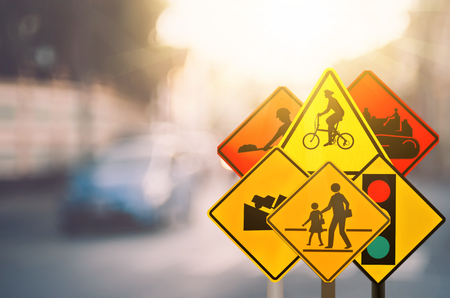 Set of traffic warning sign on blur traffic road with colorful bokeh light abstract background. Copy space of transportation and travel concept. Retro tone filter color style.
