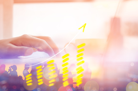 Business economic technology working concept. Woman hand using notebook double exposure graph money stock trading blur people bokeh city light abstract background. Vintage tone filter effect color style.