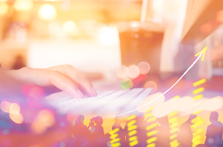 Business economic and technology working concept. Woman hand using keyboard double expose with graph money stock trading and blur people bokeh light background. Vintage tone filter effect color style.