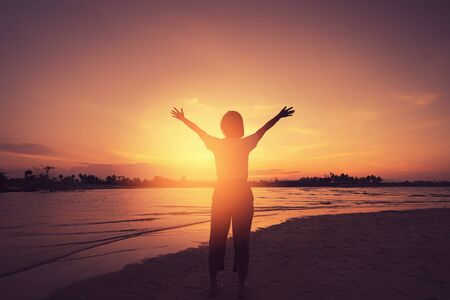 Foto de Copy space of woman rise hand up on sunset sky at beach and island background. Freedom and travel adventure concept. Vintage tone filter effect color style. - Imagen libre de derechos
