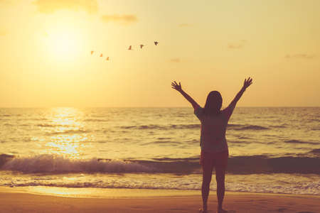 Foto de Copy space of woman raise hand up on sunset sky at beach and island with birds flying abstract background. Freedom and travel adventure concept. Vintage tone filter color style. - Imagen libre de derechos