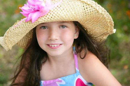 Closeup portrait of beautiful teen little girl with hat in the parkの写真素材