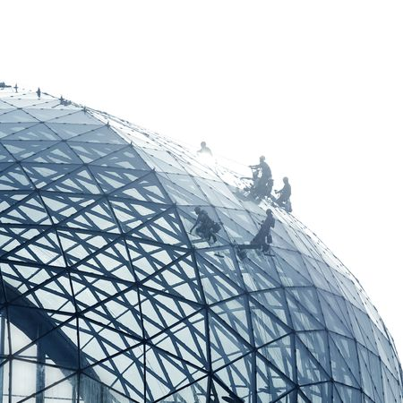 Workers cleaning a round glass facade with strong back light