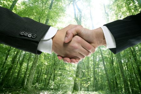 Ecological handshake businessman in a forest green background