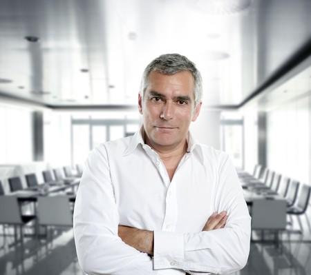 senior expertise gray hair businessman posing interior white modern office