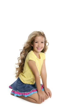 little blond girl smiling portrait on her knees isolated on white backgroundの写真素材