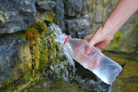 source of spring water bottle filling holding hand in Pyrenees mountain