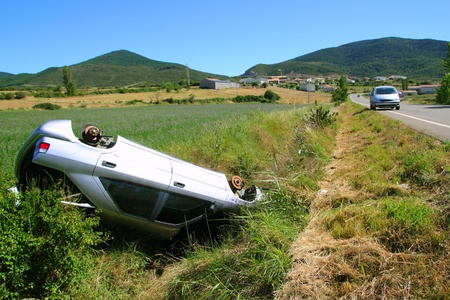 Car crash accident upside down vehicle off the road green landscape