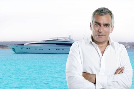 millionaire senior posing in front a luxury yacht during summer vacation