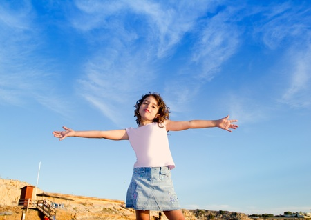 Girl open arms outdoor under blue sky with happy gesture