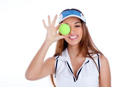 brunette tennis girl with white dress and sun visor cap with green ball
