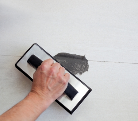 grouting tiles with rubber trowel and gray cement mortar