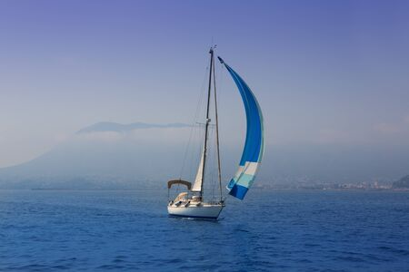 Blue sea with sailboat sailing in a foggy coast in mediterranean sea