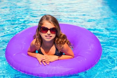 bikini kid girl with fashion sunglasses with purple inflatable pool ring