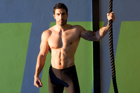 Crossfit gym handsome man holding hand a climbing rope