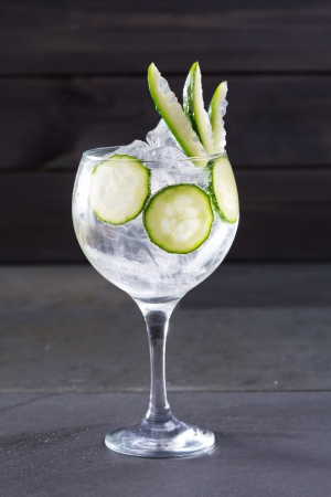 Gin tonic cocktail with cucumber and ice on black background