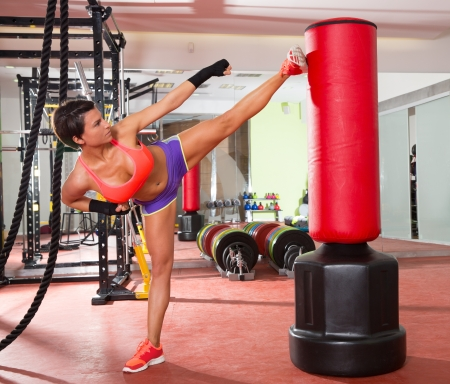 Crossfit fitness woman kick boxing with red punching bag at gym