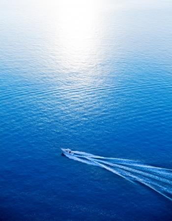 Boat cruising blue Mediterranean sea aerial view in Spain