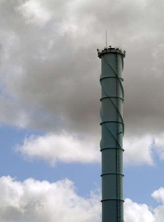 dirty looking industrial chimney set against a gloomy sky
