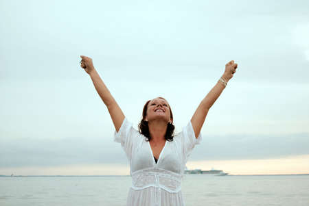 A beautiful, fit and healthy young woman throws her hands in the air in a fit of joy.