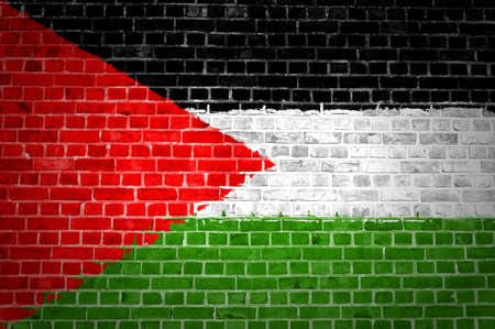 An image of the Palestine flag painted on a brick wall in an urban location