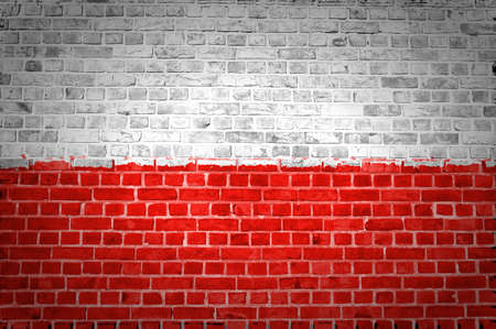 An image of the Poland flag painted on a brick wall in an urban location
