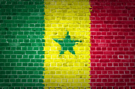 An image of the Senegal flag painted on a brick wall in an urban location