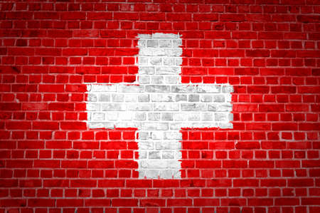 An image of the Switzerland flag painted on a brick wall in an urban location