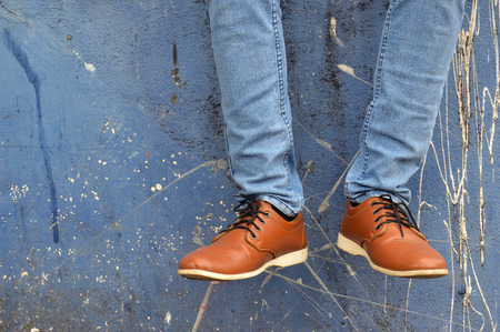 leather shoes with jeans on concrete wall