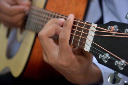 Photo pour man's fingers playing a classical wooden guitar string - image libre de droit
