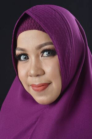 Photo pour portrait of a beautiful muslim woman wearing a violet headscarf isolated on black background - image libre de droit