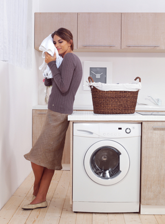 woman enjoys a smell of the washed things in laundry room