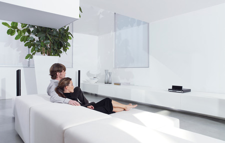 Rear view of young couple on sofa watching TV in living room