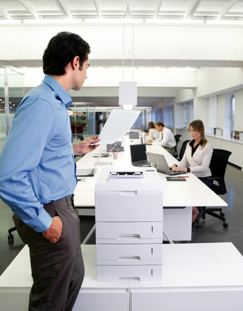 young worker using a copy machine in office