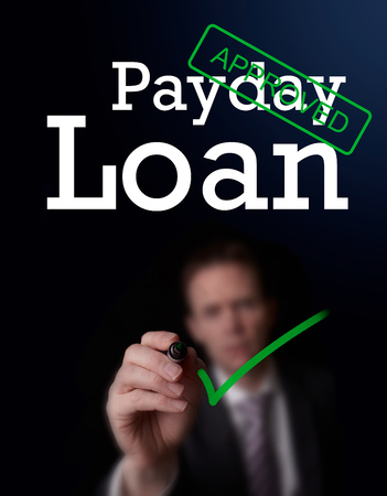 An underwriter writing Payday Loan approved on a screen.