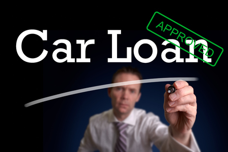 An underwriter writing Car Loan approved on a screen.