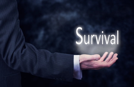 A businessmans hand holding the word, Survival.