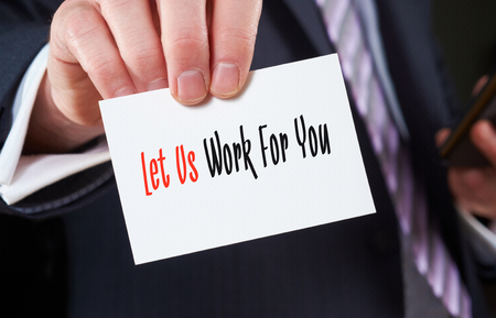 A businessman holding a business card with the words, Let Us Work For You, written on it.