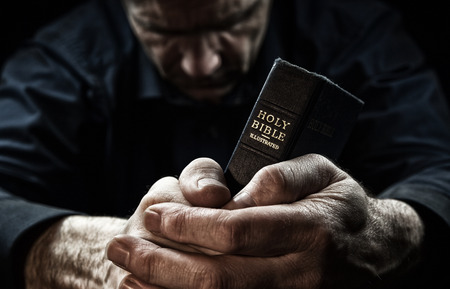 Photo for A Man praying holding a Holy Bible. - Royalty Free Image