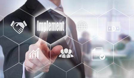Photo pour A businessman selecting a Implement Concept button on a clear screen. - image libre de droit