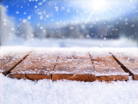 Foto de Wooden table, bench covered in snow with a Christmass, wintery and snowy background with space to add products and text.                           - Imagen libre de derechos