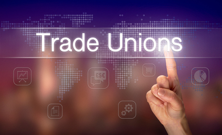 A hand selecting a Trade Unions business concept on a clear screen with a colorful blurred background.