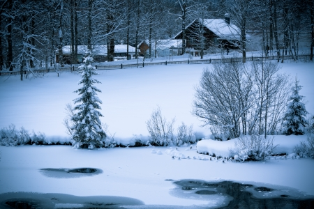 Photo pour Fairy tale. Snowy Alpine house and frozen river in the woods.ÊToned and vignetted image as postcard - image libre de droit