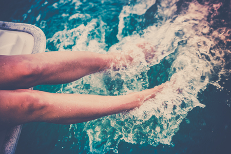 Female legs splashing sea water from a sailing yacht. Filtered shot